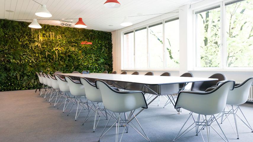 Zelená stěna džungle s aplikací loga v zasedací místnosti pro lepší akustiku